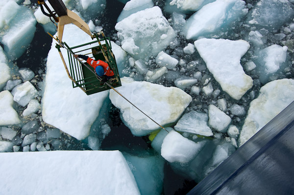 A researcher pushes ice floes away from a delicate instrument. Photo by Chris Linder, WHOI