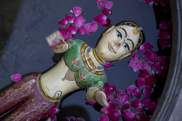 A Hindu god immersed in rose petaled water.