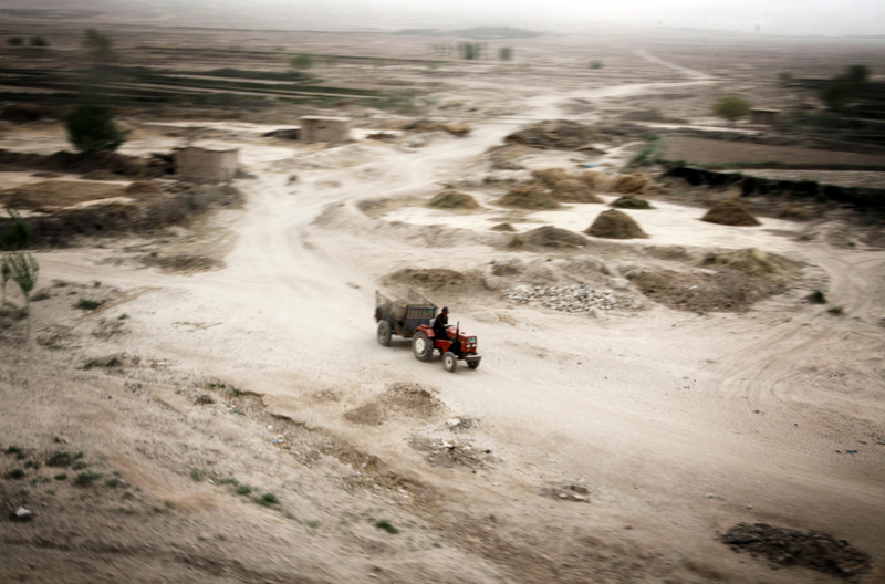 A lone farmer rides his tractor through a small rural village. ©Sean Gallagher. Courtesy Pulitzer Center for Crisis Reporting