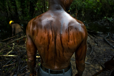 An oil spill from an abandoned Shell Petroleum Development Company well in Oloibiri, Niger Delta.  Wellhead 14 was closed in 1977 but has been leaking for years, and in June of 2004 it finally released an oil spill of over 20,000 barrels of crude. Workers subcontracted by Shell Oil Company clean it up. ©Ed Kashi