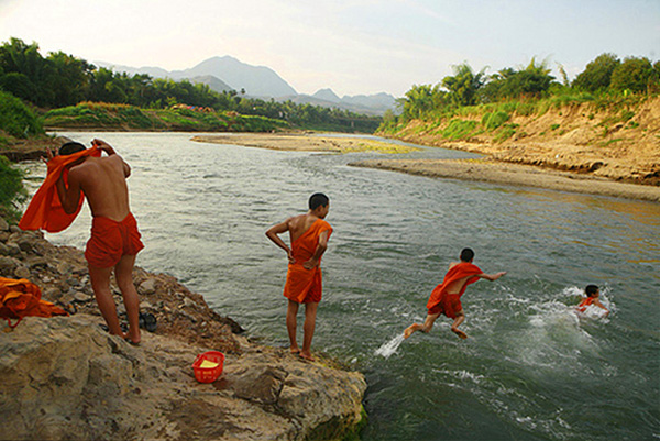 Monks from Luang Prabang disrobe and dive into the Mekong for a swim, Laos.